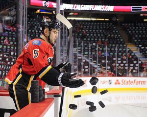 Giordano tosses pucks to fans in the stands.  Fails miserably.